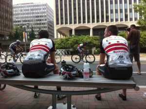 Participants in one leg of the bike race take a breather and watch the next division go by.